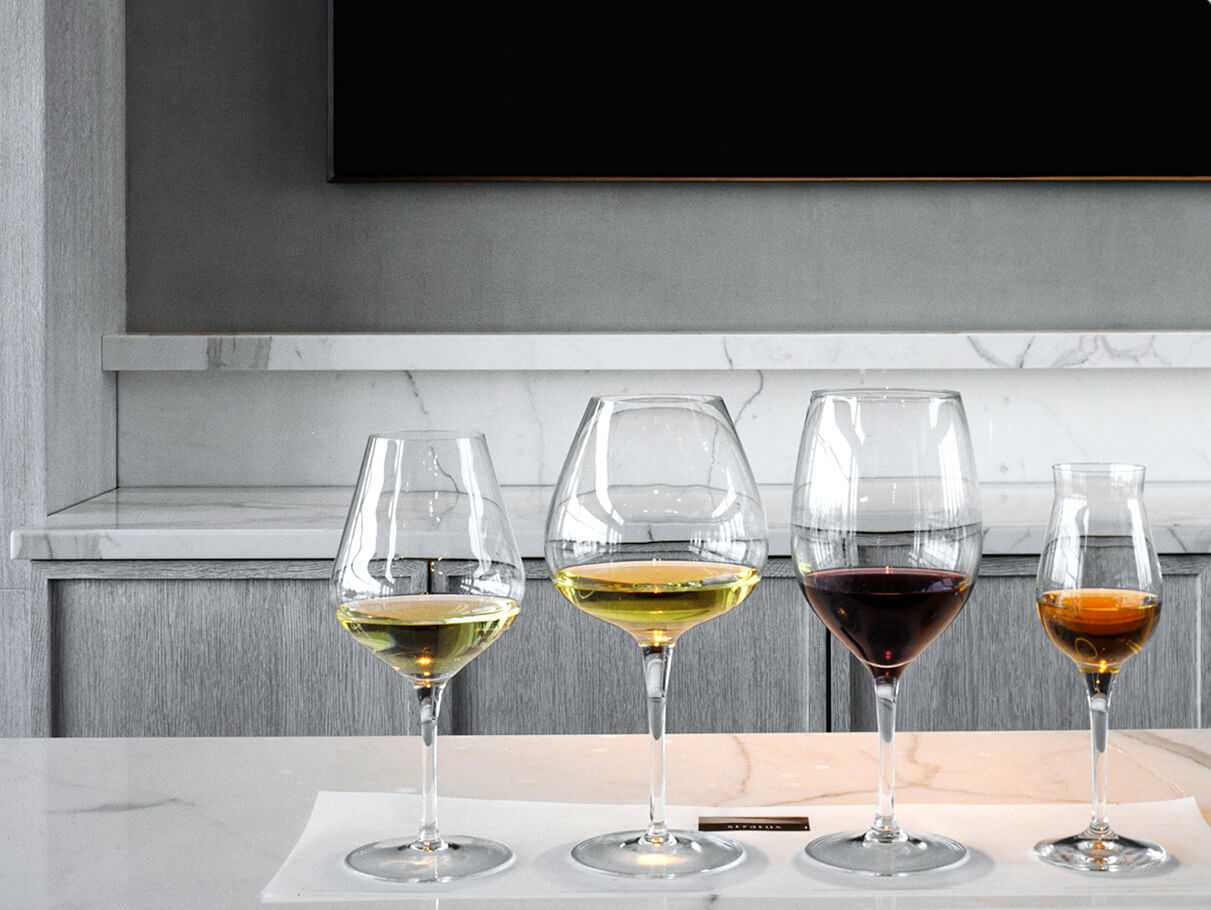 A flight of wines rests on a tasting room counter