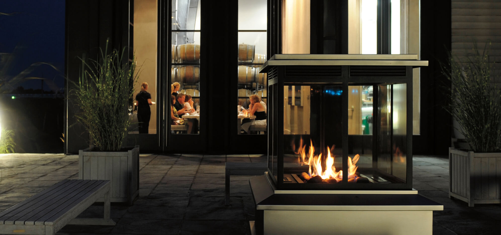 An outdoor fireplace is lit on the terrace near Stratus' wine cellar, where an event is taking place