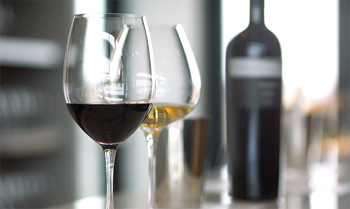 Glasses of red and white wine are positioned in front of a bottle of Stratus Red